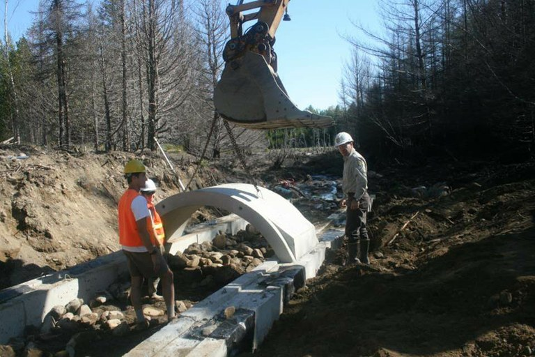 Project SHARE and MEFRO employees assist Moosehorn Refuge's excavator operator in installing a new, open-bottom, concrete culvert.